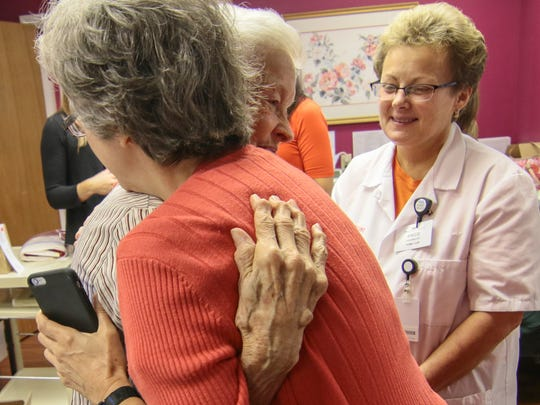Sherry Lawson, left, hugs Jo Cauthen, middle, 88, near Angie Kelley, right, at the Anderson Free Clinic Friday.