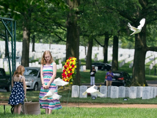 Great grand nieces Emmerson Brumbaugh, 7, and Madeline Brumbaugh, 10, both from Springfield, Virginia, release four white doves during burial services for WWII Marine Pfc. James B. Johnson of Poughkeepsie on Tuesday at Arlington National Cemetery in Arlington, Virginia.