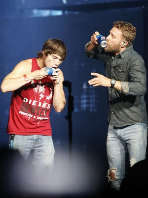 Dierks Bentley brings Hunter onto the stage to Shotgun a beer after seeing a sign in the audience at Talking Stick Resort Arena in Phoenix, Ariz. on August 26, 2017.
