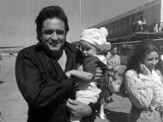 Johnny Cash carries his son John in his arms as his