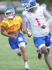 Cooper's Tyrees Whitfield, left, returns a punt while