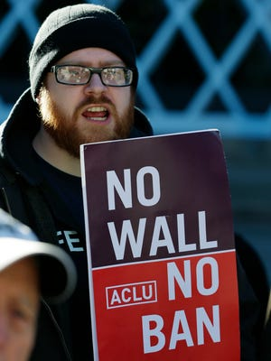 "Eric Buerk holds a sign that reads, ""No Wall No Ban,"" during a protest on Dec. 6, 2017, outside a federal courthouse in Seattle."