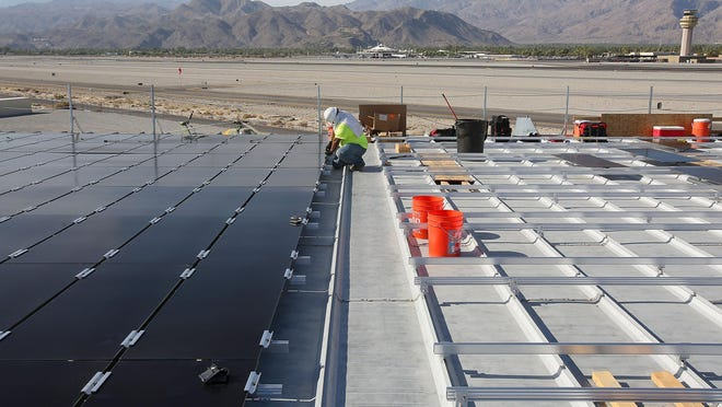 A worker with Tiger Electric installs solar panels on the roof of the Palm Springs Air Museum on Sept. 1, 2015.