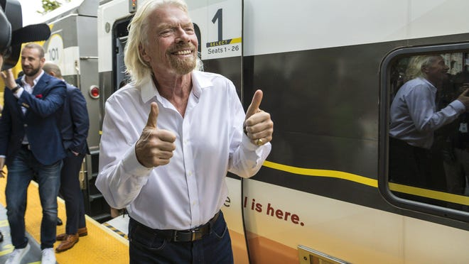 Richard Branson greets passengers in April 2019 as he arrives in West Palm Beach from Miami, where he kicked off the rebranding of Brightline's passenger trains as Virgin Trains USA.