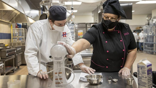 Culinary teacher Leandra Walls shows Kaleb Clark, 17, how to make chocolate mousse at Hays High School in Buda on Wednesday.