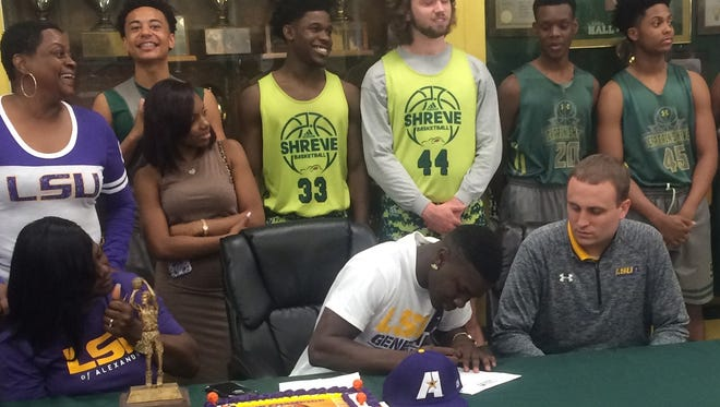 Captain Shreve senior Toronco Loston signs with LSUA as his teammates, family and Generals assistant coach Casey Apetrei look on.