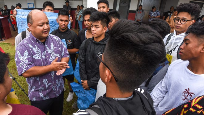 Guam Department of Education Superintendent Jon Fernandez, left, talks with students during a protest rally at Simon Sanchez High School in Yigo on Friday, April 27, 2018.