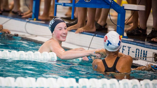 EDGE's Ella Miller (15) smiles and shakes hands after her record-breaking women's 15-18 100yd backstroke at the Vermont Swim Association Championship in White River Junction on Saturday.