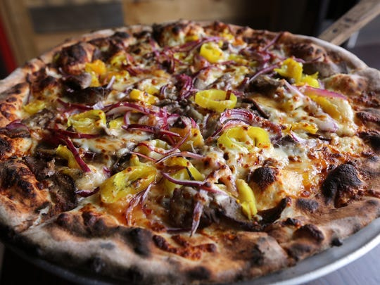 The Degrazia is a wood fired pizza with country sweet base, shaved steak, green peppers, onion and mozzarella.