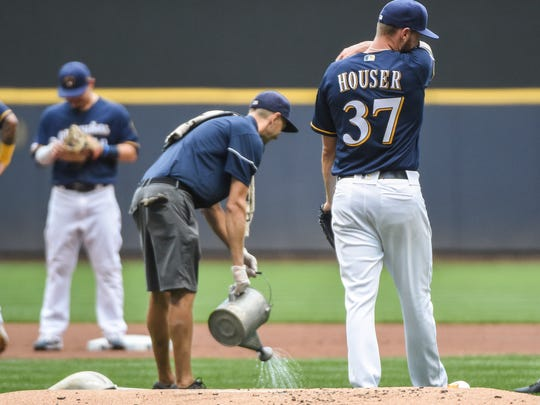 Aug 10, 2019; Milwaukee, WI, USA;  Milwaukee Brewers pitcher Adrian Houser (37) recomposes himself after he became ill as grounds crew cleanup the mess in the first inning during the game against the Texas Rangers at Miller Park. Mandatory Credit: Benny Sieu-USA TODAY Sports