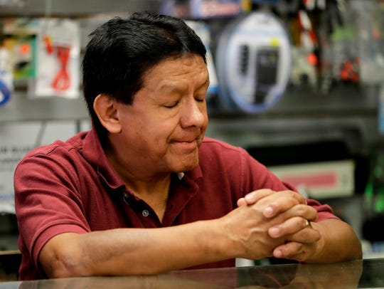 Video store owner Miguel Victoria pauses while talking