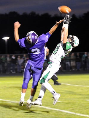 Clear Fork's Bryce Lyon reaches for a pass through Lexington's Joseph Vore's defense during the Clear Fork-Lexington game on Sept. 25, 2015. The Minutemen won 27-7.