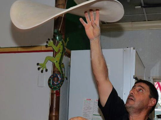 At Capri Market and Deli, Mike Castellano is busy, spinning pizza dough for the boat parade participants.
