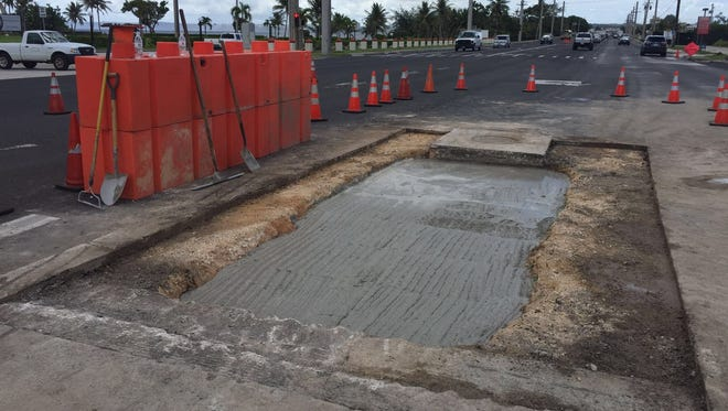 Repairs are underway on a sink hole near Adelup on Marine Corps Drive on July 12. The sink hole appeared July 11 and closed two lanes of traffic for a day.