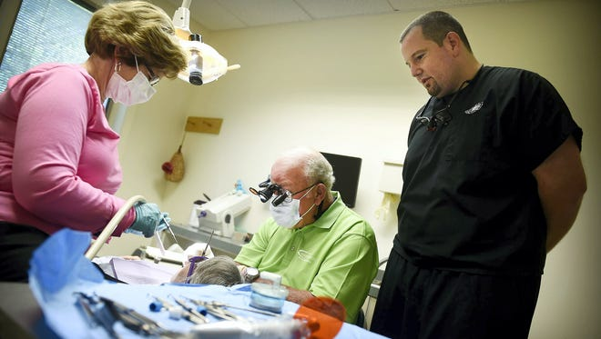 Dr.  Robert Silverman works on a patient, while Jeremy Silverman observes at Jay Day at Silverman Dental Associates in Annville in August 2015. On Jay Day, the practice offers free dental services to area residents in honor of Dr. Silverman's son, Jason Silverman, who died of leukemia.