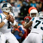 Carolina Panthers quarterback Cam Newton (1) looks to pass during the first quarter against the Arizona Cardinals in the NFC Championship football game at Bank of America Stadium.