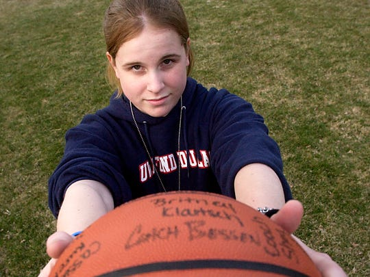 Jeanna (Giese) Frassetto holds a basketball signed by the members of the St. Mary's Springs girls' basketball team in the backyard of her family's home on April 5, 2006.