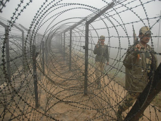 Indian Border Security Force soldiers patrol in the early morning fog along a barbed wire fence along the India Bangladesh border in Jaipur village near Agartala, capital of India's northeastern state Tripura.