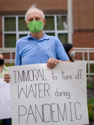 "Bruce Weik stands infront of city hall protesting water shutoffs while holding a sign that reads ""immoral to turn off water during pandemic""."