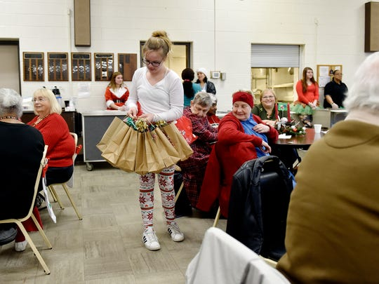 Ann-Marie Wolfe, 12 of Stewartstown, hands out gift bags to seniors at the White Rose Senior Center Thursday in York. She and her older sisters Hailey, 16, and Rylee, 13, collected donations from various businesses and spent their own Christmas money toward items for 100 gift bags for seniors at the center, where they distributed the bags and helped serve lunch.