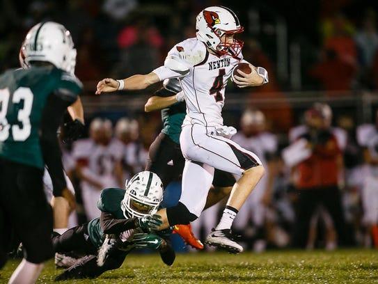 Newton's Garrett Sturtz is tackled by Des Moines North's