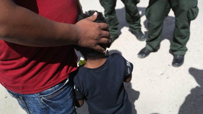 U.S. Border Patrol agents take a father and son from Honduras into custody near the U.S.-Mexico border on June 12, 2018, near Mission, Texas.