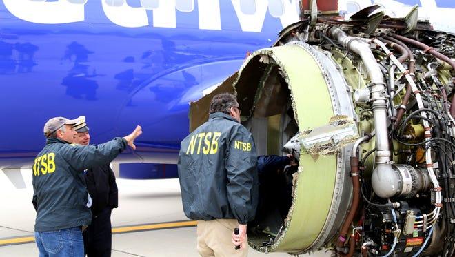 In this National Transportation Safety Board handout, investigators examine damage to the CFM International 56-7B turbofan engine belonging Southwest Airlines Flight 1380 that separated during flight at Philadelphia International Airport April 17, 2018 in Philadelphia, Pennsylvania.