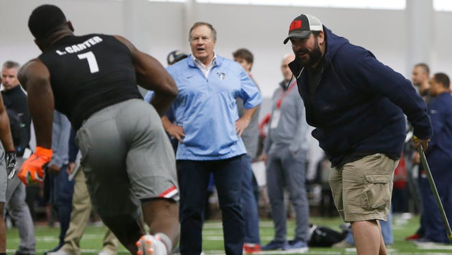 Georgia linebacker Lorenzo Carter works with Detroit Lions coach Matt Patricia, right, and New England Patriots coach Bill Belichick, center, during Georgia Pro Day, March 21, 2018 in Athens.