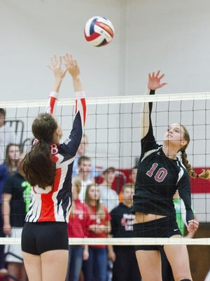 Manitowoc Lutheran's Lindsay Engelbrecht (10) hits a ball over the net while Cedar Grove-Belgium's Vanessa Depies tries to block Tuesday at Manitowoc Lutheran.