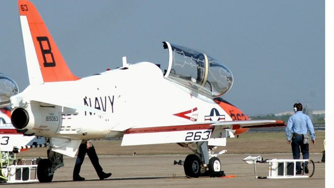 A T-45 Goshawk training jet is prepared for daily training operations on the ground, while another takes flight just above it at Naval Air Station Kingsville in 2002.