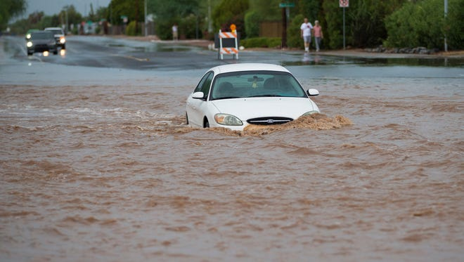 A car rests in floodwaters after a women was rescued when her car got stuck on west 16th Avenue in Apache Junction on July 24, 2017.