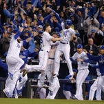 Kansas City Royals players celebrate after Alcides Escobar scored on a sacrifice fly by Eric Hosmer during the 14th inning of Game 1 of the World Series against the New York Mets Wednesday, Oct. 28, 2015, in Kansas City, Mo.