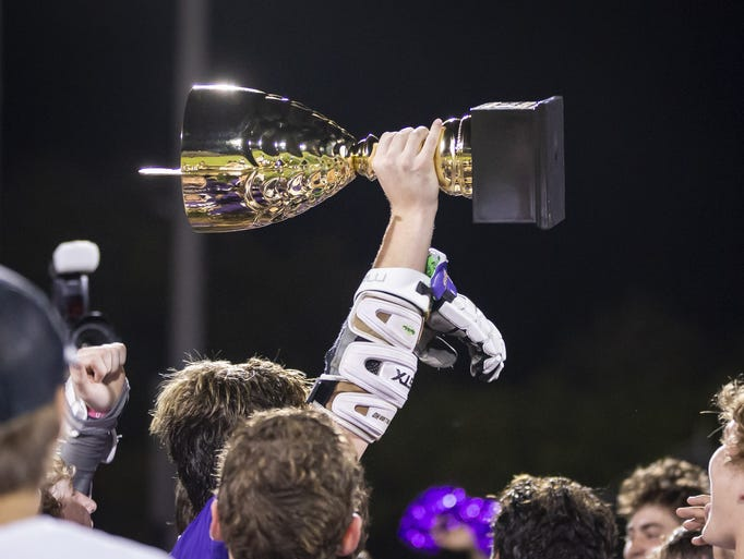 The Notre Dame Prep Saints hold up their trophy following
