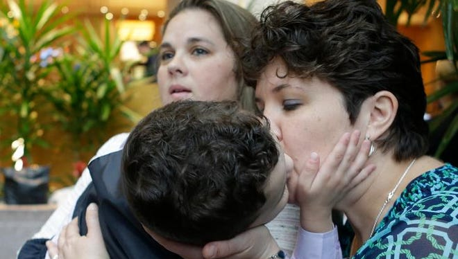 Nicole Yorksmith, right, kisses her three-year-old biological son while he is held by her spouse, Pam Yorksmith, during a news conference, Friday, April 4, 2014, in Cincinnati. Civil rights attorneys are arguing in Federal Court on Friday that a federal judge should prohibit Ohio officials from enforcing the state's ban on gay marriage.