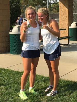 Seaman tennis players Grace Unruh, left, and Lauren Sweeney hold their medals after winning the doubles championship in Monday's Centennial League tournament.
