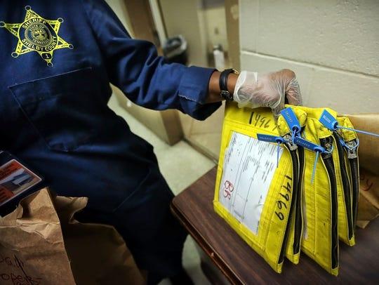 A Sheriff's Deputy stores personal belongings taken