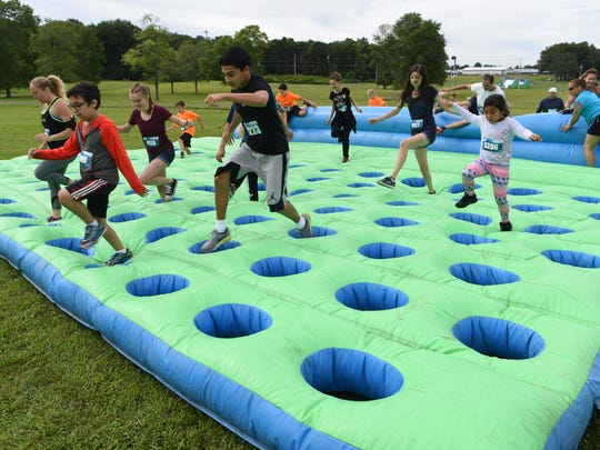 Runners hop through one of the inflatables during the