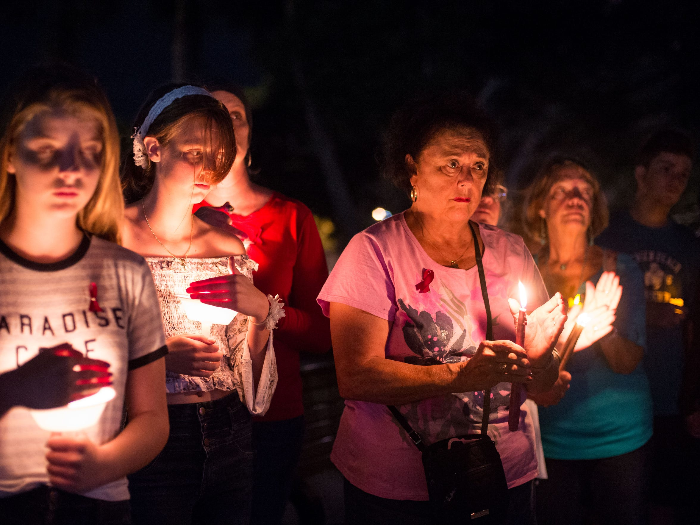 Nearly a hundred people attend a candlelight vigil at Memorial Park in downtown Stuart on Monday, Feb. 19, 2018, to honor the victims of last week's mass shooting at Marjorie Stoneman Douglas High School in Parkland. The vigil, which was organized by Florida PTA, was one of several held simultaneously across the state.