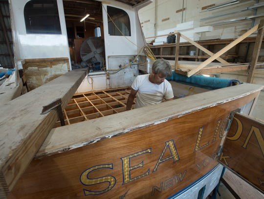 Don Breheny works on reinstalling the deck on the stern