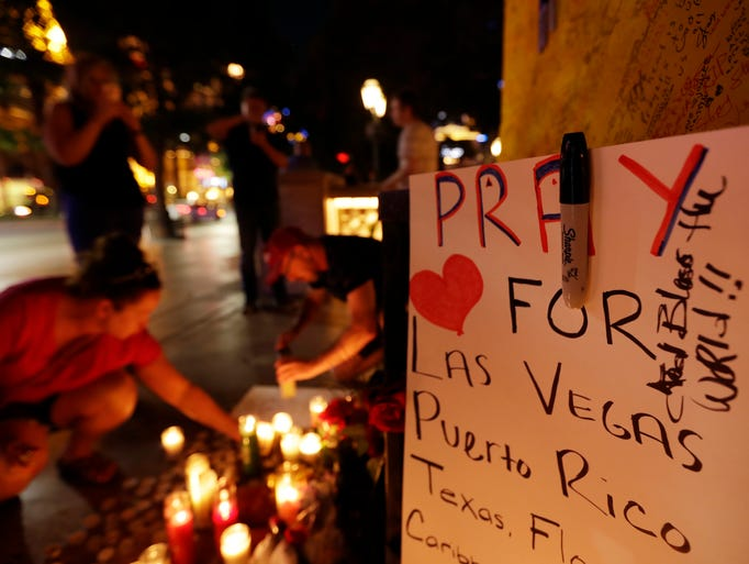 People pause at a memorial set up for victims of a