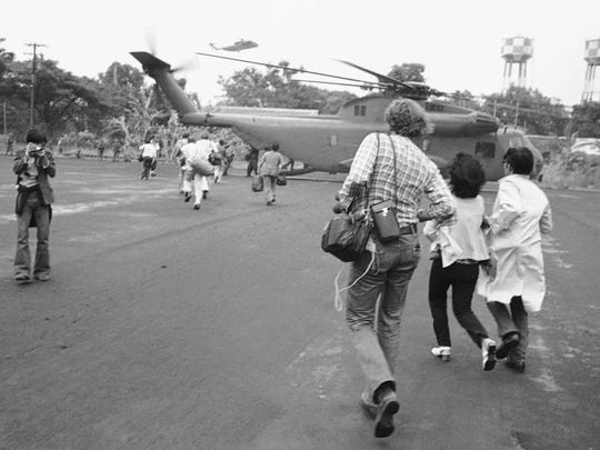 Americans and Vietnamese run for a U.S. Marine helicopter
