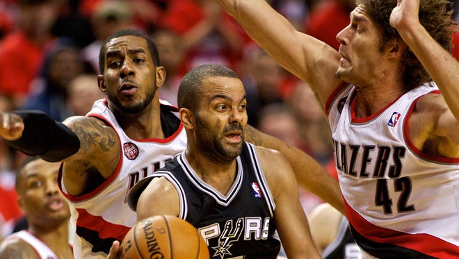 San Antonio Spurs guard Tony Parker (9) passes the ball in fron tof Portland Trail Blazers forward LaMarcus Aldridge (12) and center Robin Lopez (42) during the third quarter in game three of the second round of the 2014 NBA Playoffs at the Moda Center.