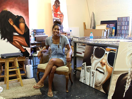 Artist Torri Smith in her studio. The two paintings