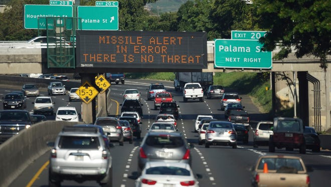 "In this Jan. 13, 2018, file photo provided to the Associated Press by Civil Beat, cars drive past a highway sign that says ""MISSILE ALERT ERROR THERE IS NO THREAT"" on the H-1 Freeway in Honolulu."