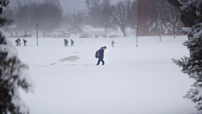 Augustana freshman Jenna Siganos walks to class in the snow Wednesday, April 18, at the university in Sioux Falls. Sioux Falls received 6.2 inches by 11 a.m. according to the National Weather Service.