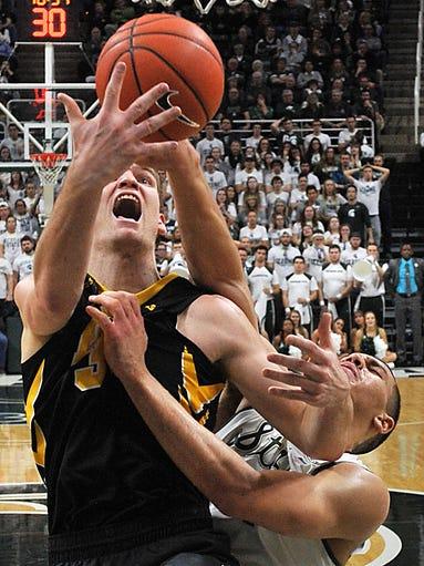 Iowa's Adam Woodbury and MSU's Gavin Schilling get