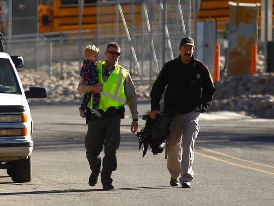 San Juan County sheriff's deputies carry away a child