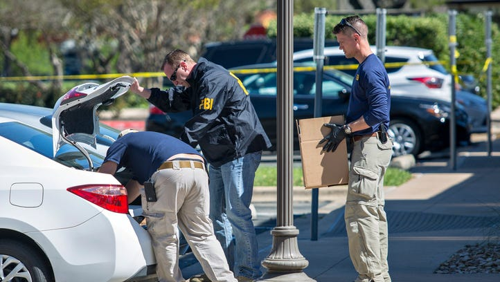 FBI agents are seen carrying items out in paper bags