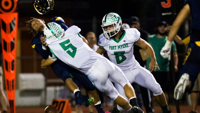 Naples High School junior, Jordan Persade-tirone, falls to the ground and loses his helmet as Fort Myers High School senior, Dawson Degroot, tackles him during the Class 6A regional semifinal at Naples High School on Friday, November 18, 2016 in Golden Gate.