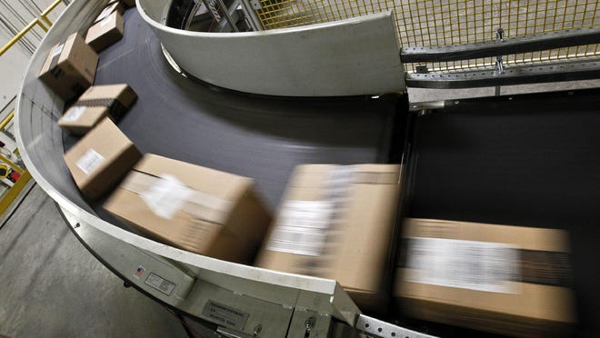 Packages ready to ship move along a conveyor belt at an Amazon fulfillment center.